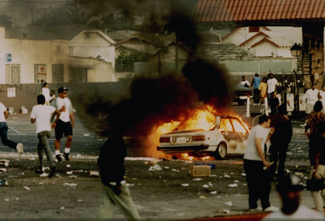 A car burns as looters take to the streets at the intersection of Florence and Normandie Avenues