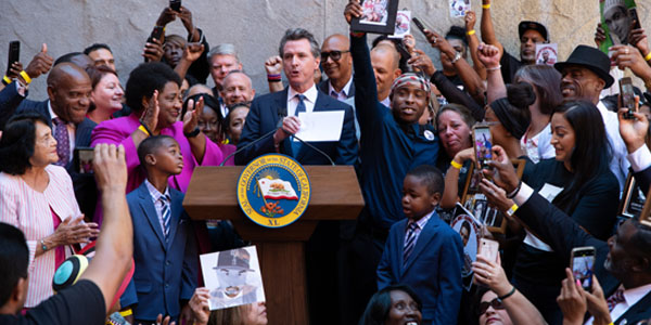 "Governor Gavin Newsom signs AB 392 ""California Act to Save Lives"" with family members and advocates standing by his side along with the author Assemblymember, Dr. Shirley Weber (D-San Diego) and legislative leaders August 19, 2019. Photo by Robert Maryland, CBM"