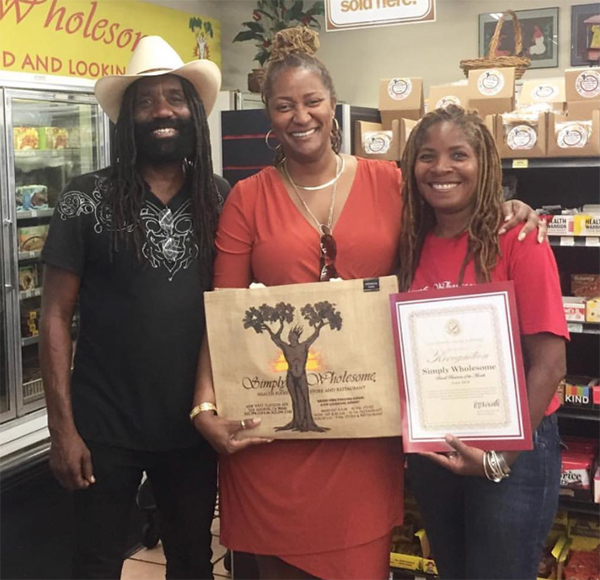 Percell Keeling owner of Simply Wholesome stands with state Sen.Holly Mitchell and Apryl Sims, operations manager being honored as the senator's business of the year.