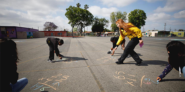 Kids working on math problems at a Los Angeles school with a City Year AmeriCorps advisor.