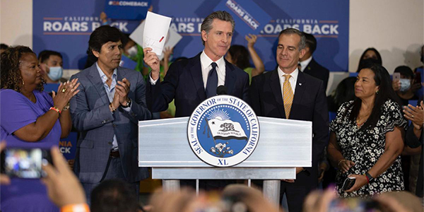 Photo credit: California Governor Gavin Newson holds a copy of the state's 2021-2022 budget, which he signed July 12. (photo courtesy of Governor Gavin Newsom's office)